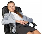 Businesswoman back in office chair, with hands clasped over her stomach