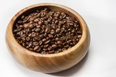 Heap Of Roasted Aromatic Coffee Beans Placed In Wooden Bowl Over White Surface.