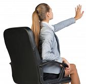 Businesswoman on office chair, with her hand reached upwards and ahead, palm outward