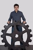 Young Man Holding A Large Gear
