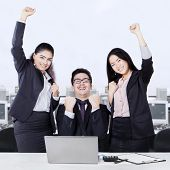 Successful Business Team Celebrating With Arms Up