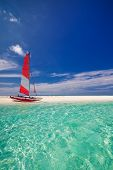 image of deserted island  - Sailing boat with red sail on beach of deserted tropical island - JPG