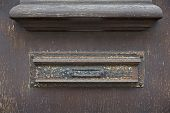 Mail slot on a weathered wooden door
