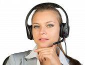 Businesswoman in headset sitting on chair, hand under chin
