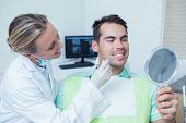 Female dentist examining mans teeth in the dentists chair