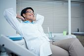 Relaxed smiling female dentist sitting on chair with hands behind head