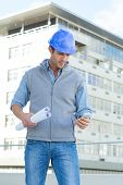 Male architect with blueprints reading text message thought mobile phone outside building