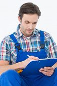 Plumber writing notes on clipboard over white background