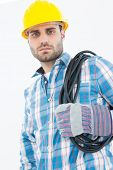 Portrait of confident repairman carrying pipe on shoulder against white background