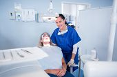 Dentist sitting over patient in the chair at the dental clinic