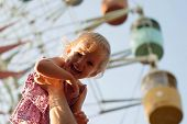 Girl On Dad Hands Near The Observation Wheel