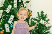 Little Girl Posing Near The Christmas Tree Decorated With Dollars