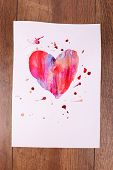 Painted heart on sheet of paper on wooden table background