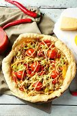 Vegetable pie with paprika, tomatoes and cheese on wooden background