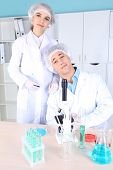 Male and female scientists with microscope in laboratory
