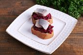 Rye toasts with herring and beets on plate on wooden background