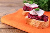 Rye toasts with herring and beets on napkin on wooden table