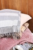 warm plaids and pillow on rustic wooden background