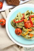 Tasty pasta with pepper, carrot and tomatoes on wooden table background