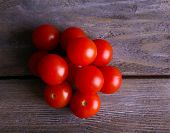 Pile of cherry tomatoes on rustic wooden planks background