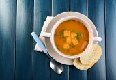 Carrot soup in bowl, on color wooden background