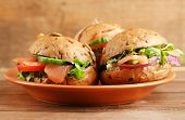 Sandwiches with salmon on plate, on wooden background