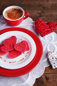 Cookies in form of heart in plate with cup of coffee on napkin, on rustic wooden planks background