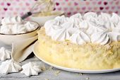 Tasty homemade meringue cake on wooden table, on pink background