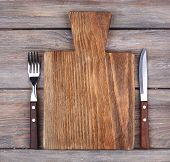 Cutting board with fork and knife on rustic wooden planks background