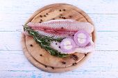 stock photo of pangasius  - Pangasius fillet with herb and spices on cutting board and color wooden table background - JPG