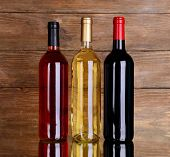 Different bottles of wine on table on wooden background