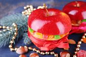 Red apples stuffed with dried fruits with cinnamon, sprig of fir tree and nuts on color wooden table background