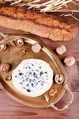Blue cheese with nuts, baguette and hay on metal tray and wooden table background