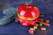 Red apple stuffed with dried fruits with cinnamon, sprig of fir tree and almond on color wooden background