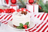 Delicious cake on saucer with holly and berry on Christmas decoration background