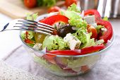 Greek salad in glass dish with fork and vegetables background