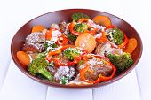 Braised wild mushrooms with vegetables and sauce in plate on table