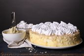 Tasty homemade meringue cake on wooden table, on grey background
