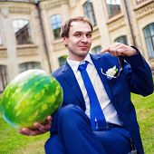 serious man holding watermelon and shows a finger at him