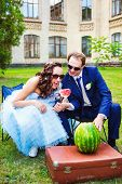 bride and groom eating watermelon at the picnic