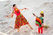 Boy dressed in Mexican costume holding a toy gun and plays with his mother