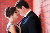 Bride and groom on a red wall background