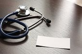 A blank and a blue stethoscope on a desktop