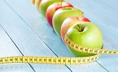 Apples with tape measure on blue wood background, lose weight concept