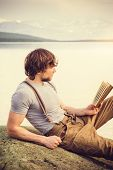 picture of scandinavian  - Young Man reading book outdoor with scandinavian lake and mountains on background Education and Lifestyle Travel concept - JPG