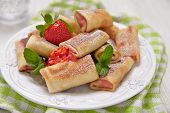 stock photo of crepes  - Fresh Strawberry Crepes Rolls with Mint for Breakfast - JPG