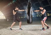 stock photo of sandbag  - Two boxers hitting the sandbag  - JPG