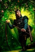 stock photo of bow arrow  - Portrait of a male elf with a bow and arrows in a magical forest - JPG