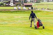 pic of caddy  - a golf player playing on a beautiful golf course and a golf bag full of golf clubs - JPG