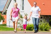 image of children walking  - Family of Parents and child walking in front of home in village or suburb - JPG